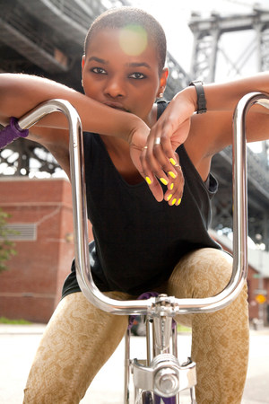 sleek: Portrait of a young woman leaning on bicycle handlebars