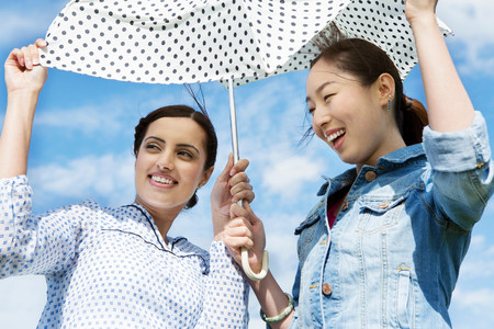 Two young women outdoors with parasol LANG_EVOIMAGES