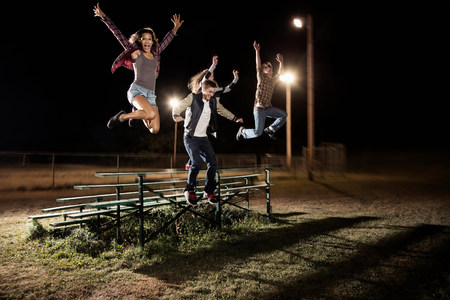 liberating: Four friends jumping over bleachers at night LANG_EVOIMAGES