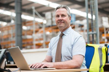 technology: Man using laptop in warehouse,portrait