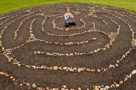 way out: Woman meditating in stone labyrinth