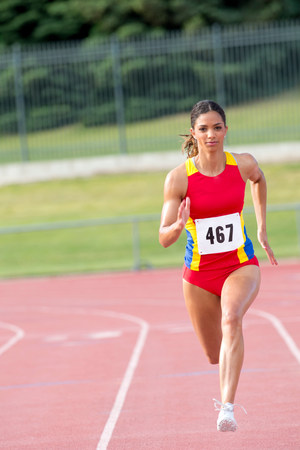 Female athlete running on track LANG_EVOIMAGES