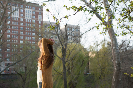 towerblock: Young woman standing in the park LANG_EVOIMAGES