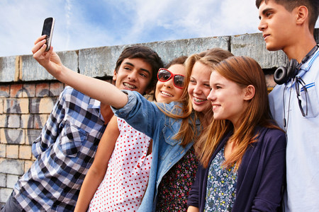 Teenage friends photographing themselves with smartphone LANG_EVOIMAGES