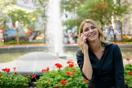 Happy businesswoman on phone in park LANG_EVOIMAGES