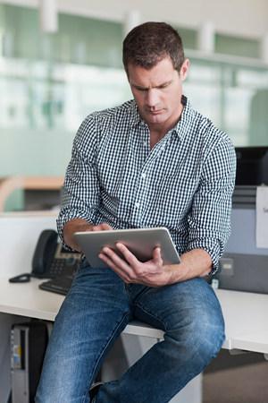 engrossed: Man concentrating on digital tablet
