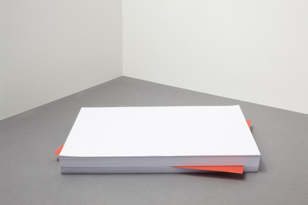 Red piece of paper amongst stack of blank paper