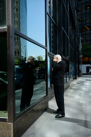 sidewalk talk: Businessman looking at reflection in building window LANG_EVOIMAGES