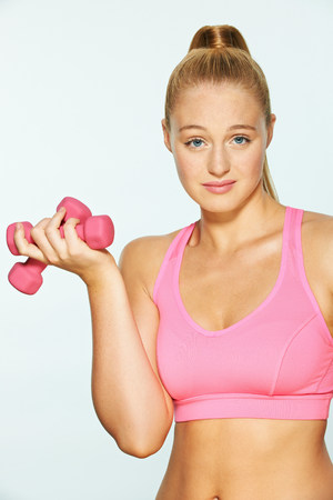 Young woman using hand weights,looking unimpressed