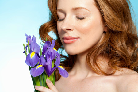 half naked: Woman smelling purple flowers