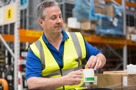 one mature man only: Man on tea break in warehouse LANG_EVOIMAGES