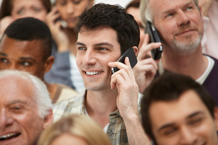 Man on cell phone with group of people