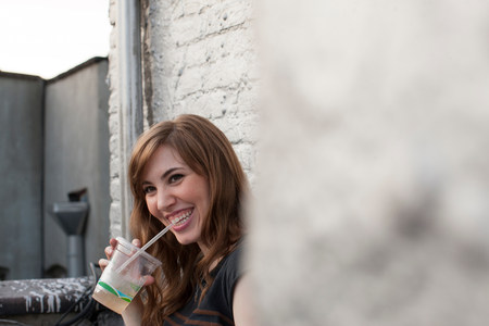 Young woman drinking and smiling