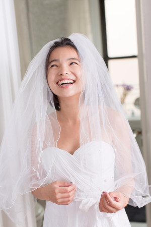 Young woman wearing wedding dress and laughing