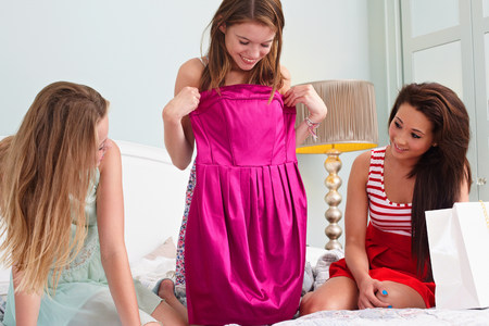 3 persons only: Teenage girl showing dress to friends LANG_EVOIMAGES