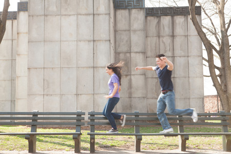 socialise: Young couple running along benches LANG_EVOIMAGES