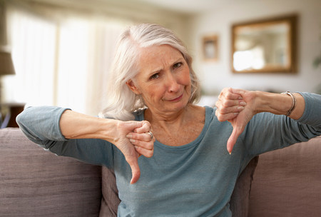 displeased: Senior woman with thumbs down LANG_EVOIMAGES