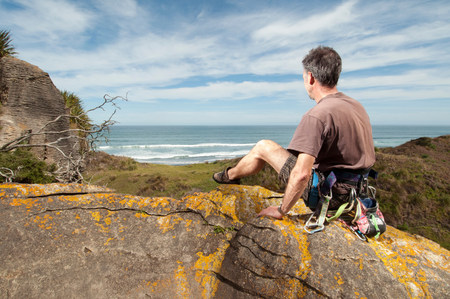 trouble free: Rock climber at top of rock taking in scenery,Ruapuke,Raglan,New Zealand LANG_EVOIMAGES