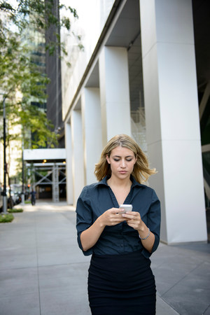 engrossed: Businesswoman walking and texting on cellphone LANG_EVOIMAGES