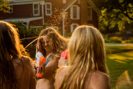 Girls having water fight with water pistols