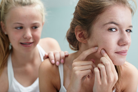 revulsion: Girl squeezing a spot,friend with hand on shoulder