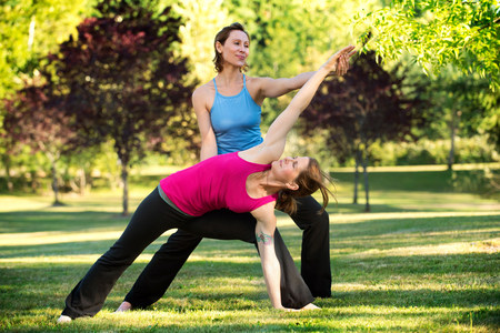 Yoga instructor and student in park