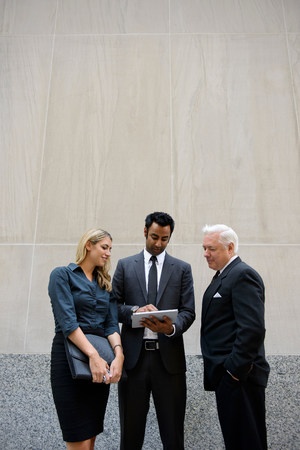 age 20 25 years: Three businesspeople looking at a digital tablet