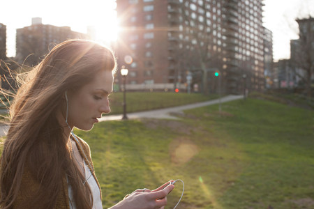 towerblock: Young woman listening to music in park