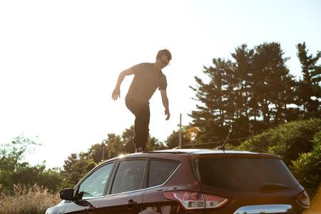 low self esteem: Young man walking across car roof
