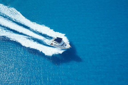 Motor yacht ploughing across blue sea LANG_EVOIMAGES