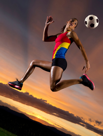 athleticism: Female footballer in mid air against sunset