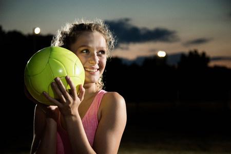 Muchacha que sostiene el balón de fútbol en la noche LANG_EVOIMAGES