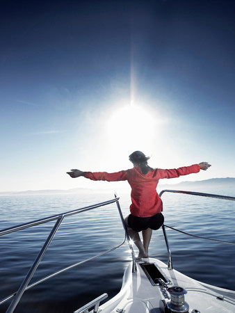 Woman on bow of sailing boat with arms outstretched