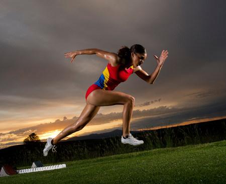 Female athlete leaving starting blocks LANG_EVOIMAGES