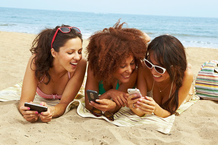 human likeness: Young women on beach with cell phones