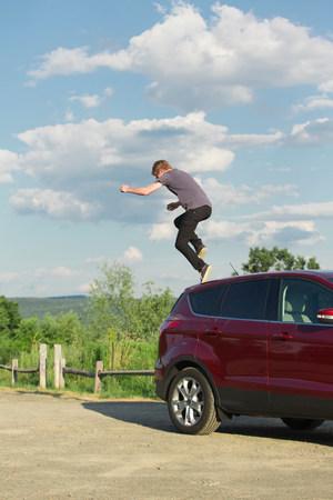 Young man jumping off car