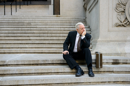 Sad businessman on steps LANG_EVOIMAGES