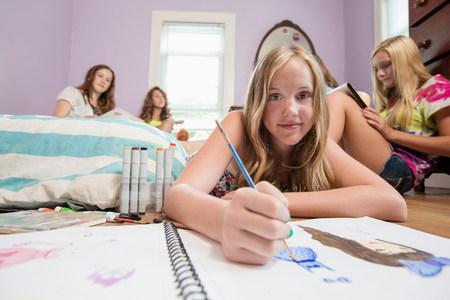 tweens: Girl drawing in notebook LANG_EVOIMAGES