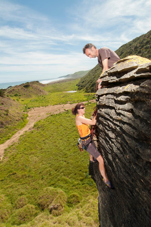 Rock climbers scaling rock,Ruapuke,Raglan,New Zealand LANG_EVOIMAGES