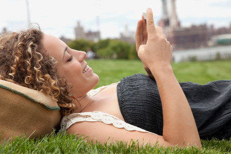 Young woman lying on grass and looking at smartphone LANG_EVOIMAGES