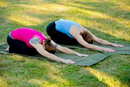 arrodillarse: Dos mujeres que se extiende en las esteras de yoga al aire libre LANG_EVOIMAGES