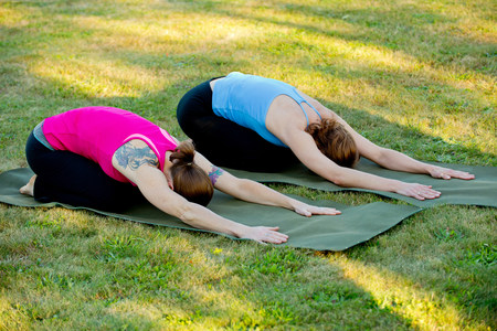 Two women stretching on yoga mats outdoors