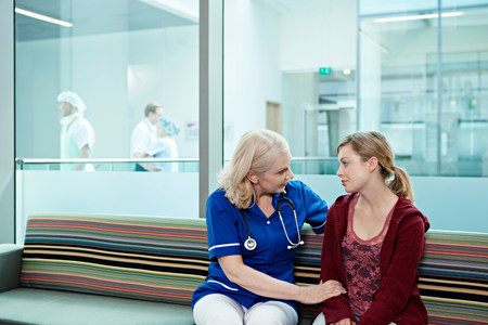 age 25 30 years: Nurse talking to woman in hospital waiting room LANG_EVOIMAGES