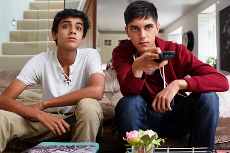 remote controls: Teenage boys watching television