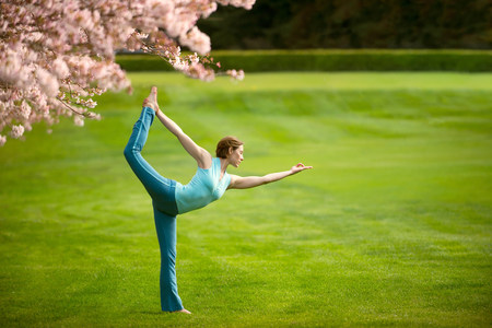 Woman in standing bow yoga position in park