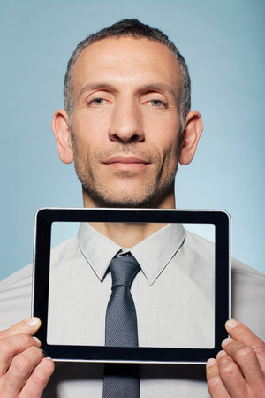 Man covering neck with digital tablet LANG_EVOIMAGES