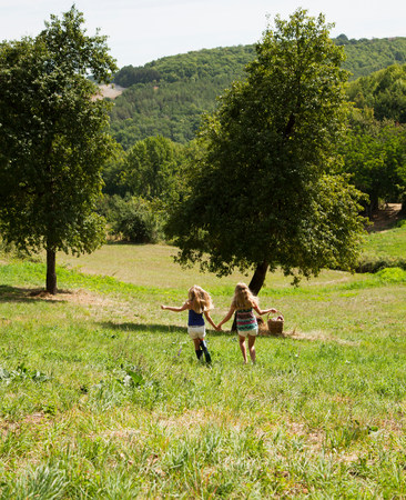 liberating: Two girls holding hands in field