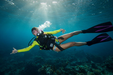 all under 18: Woman scuba diving in tropical water