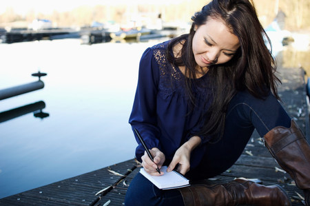 liberating: Woman making notes on wooden deck LANG_EVOIMAGES