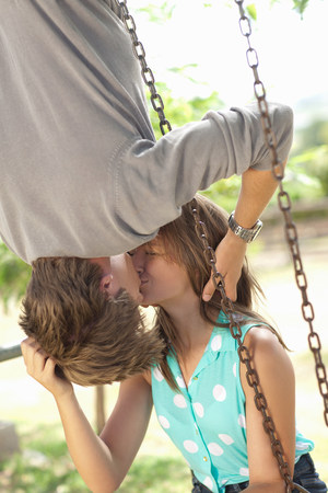 Couple kissing on swing set